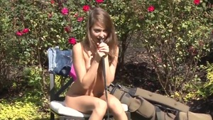 Horny chick bends over in the garden solo